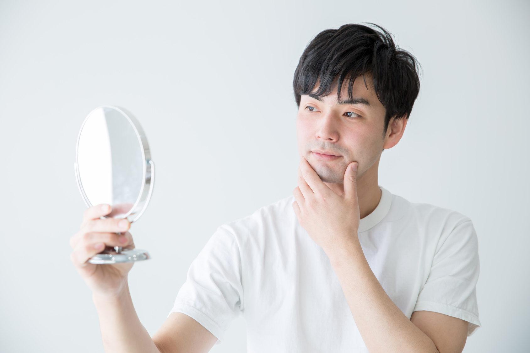 写真:鏡を見る男性